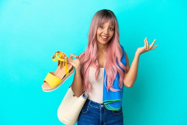 Jeune femme métisse aux cheveux roses tenant des sandales d'été isolées sur fond bleu tendant les mains sur le côté pour inviter à venir