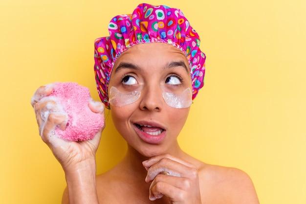 Jeune femme métisse avec bonnet de douche tenant une éponge isolé sur fond jaune