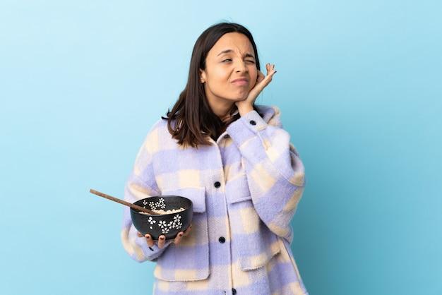 Jeune femme métisse brune tenant un bol plein de nouilles sur bleu isolé frustré et couvrant les oreilles