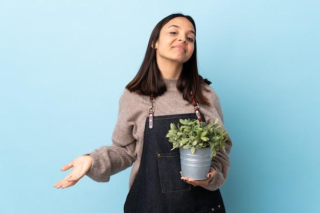 Jeune femme métisse brune tenant une plante sur bleu isolé ayant des doutes