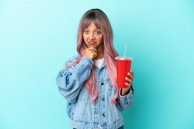 Jeune femme métisse buvant une boisson fraîche isolée sur fond bleu pensant