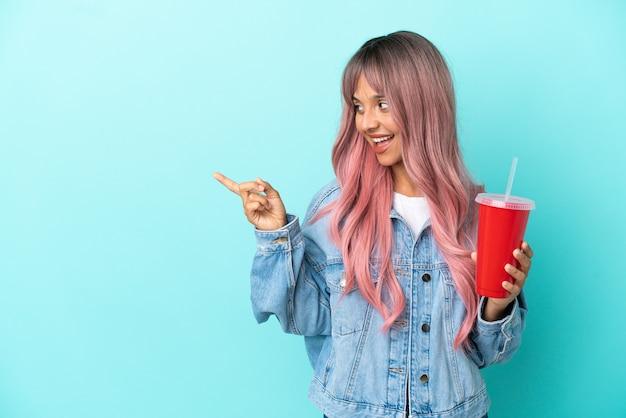 Jeune femme métisse buvant une boisson fraîche isolée sur fond bleu pointant le doigt sur le côté et présentant un produit