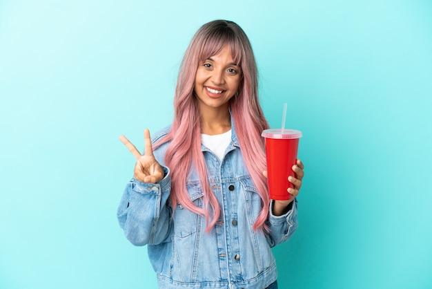 Jeune femme métisse buvant une boisson fraîche isolée sur fond bleu souriant et montrant le signe de la victoire