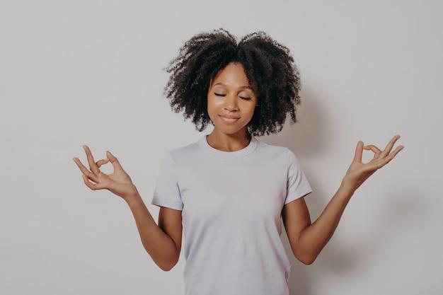 Jeune femme métisse calme et paisible gardant les mains dans le geste de mudra et les yeux fermés