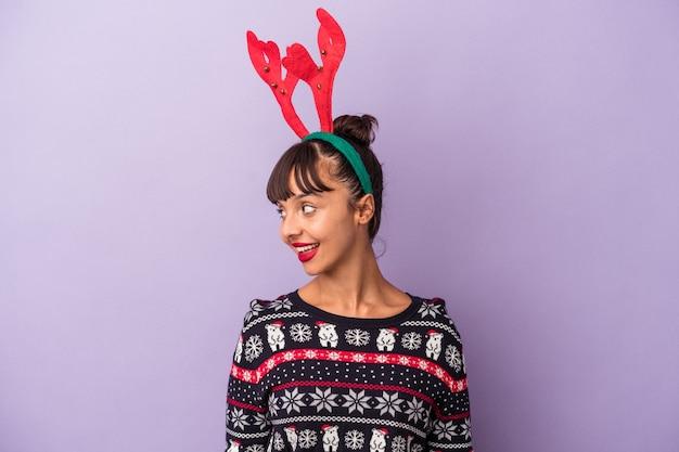 Jeune femme métisse avec chapeau de renne célébrant noël isolé sur fond violet regarde de côté souriant, joyeux et agréable.