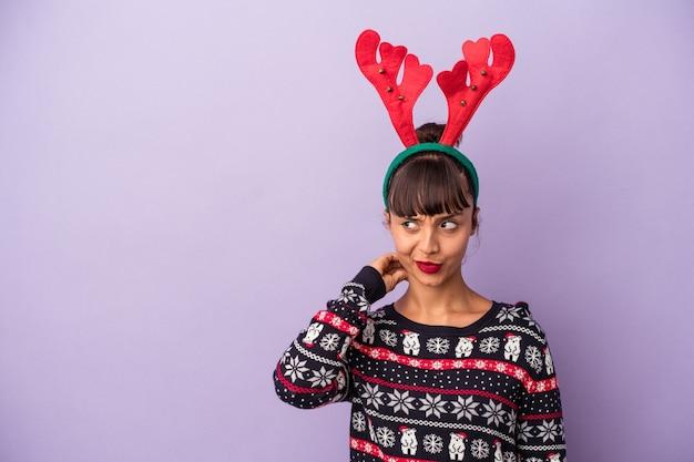 Jeune femme métisse avec chapeau de renne célébrant noël isolé sur fond violet touchant l'arrière de la tête, pensant et faisant un choix.