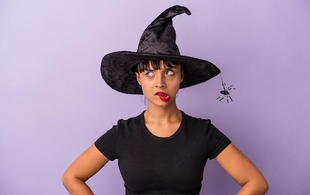 Jeune femme métisse déguisée en sorcière isolée sur fond violet confuse, se sent dubitative et incertaine.
