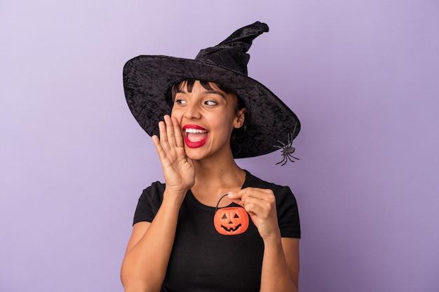 Jeune femme métisse déguisée en sorcière isolée sur fond violet criant et tenant la paume près de la bouche ouverte.