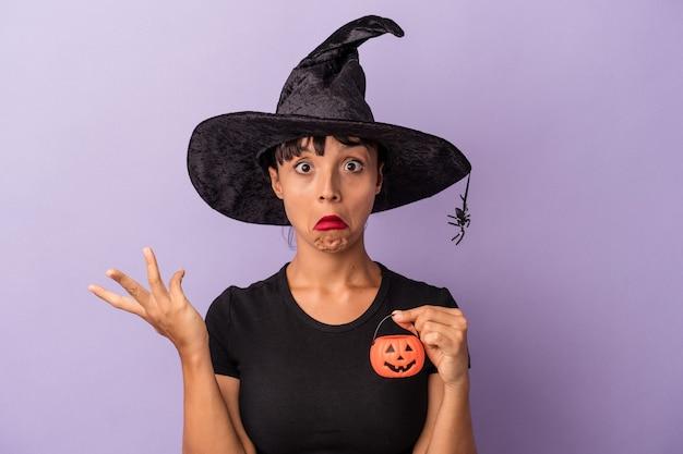 Jeune femme métisse déguisée en sorcière isolée sur fond violet hausse les épaules et ouvre les yeux confus.