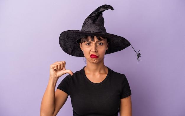 Jeune femme métisse déguisée en sorcière isolée sur fond violet montrant un geste d'aversion, les pouces vers le bas. notion de désaccord.