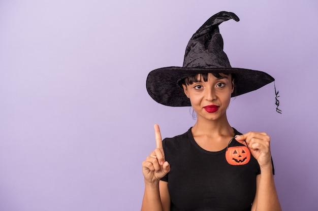 Jeune femme métisse déguisée en sorcière isolée sur fond violet montrant le numéro un avec le doigt.