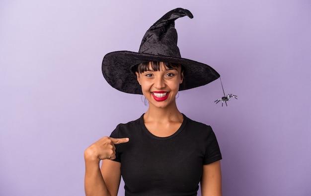 Jeune femme métisse déguisée en sorcière isolée sur fond violet personne pointant à la main vers un espace de copie de chemise, fière et confiante