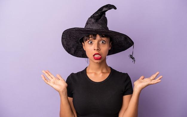 Jeune femme métisse déguisée en sorcière isolée sur fond violet surprise et choquée.