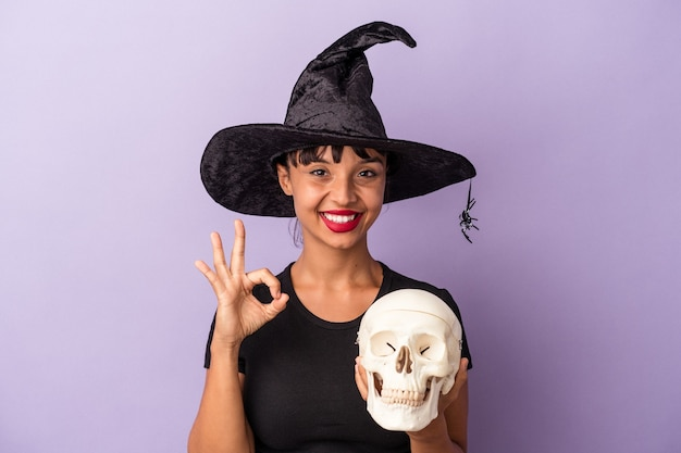 Jeune femme métisse déguisée en sorcière tenant un crâne isolé sur fond violet joyeux et confiant montrant un geste correct.