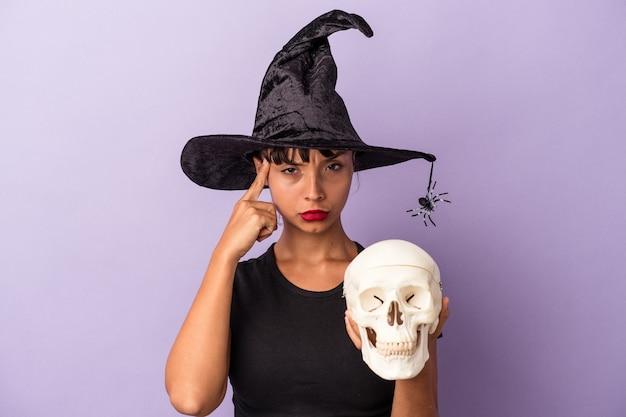 Jeune femme métisse déguisée en sorcière tenant un crâne isolé sur fond violet pointant le temple avec le doigt, pensant, concentré sur une tâche.