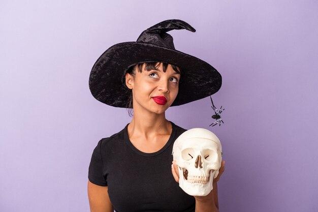 Jeune femme métisse déguisée en sorcière tenant un crâne isolé sur fond violet rêvant d'atteindre des objectifs