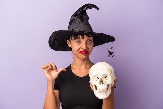 Une jeune femme métisse déguisée en sorcière tenant un crâne isolé sur fond violet se sent fière et confiante, exemple à suivre.