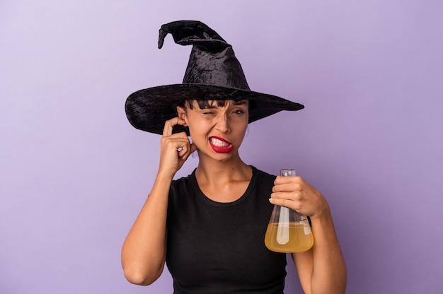 Jeune femme métisse déguisée en sorcière tenant une potion isolée sur fond violet couvrant les oreilles avec les mains.