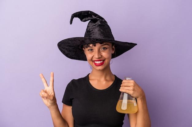 Jeune femme métisse déguisée en sorcière tenant une potion isolée sur fond violet montrant le numéro deux avec les doigts.