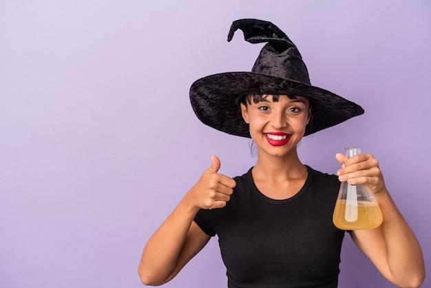 Jeune femme métisse déguisée en sorcière tenant une potion isolée sur fond violet souriant et levant le pouce vers le haut