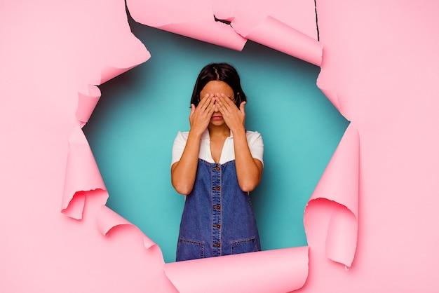 Jeune femme métisse derrière un fond cassé ayant une forte douleur dentaire, une douleur molaire.