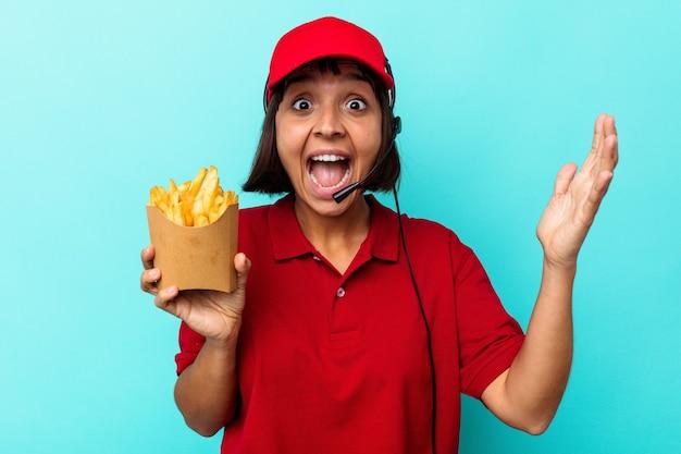 Jeune femme métisse employée de restauration rapide tenant des frites isolées sur fond bleu recevant une agréable surprise, excitée et levant les mains.