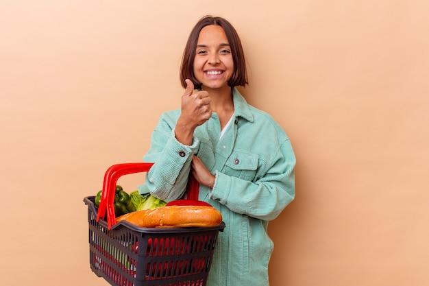 Jeune femme métisse faisant le shopping isolé sur mur beige