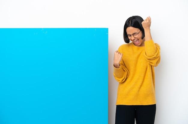 Jeune femme métisse avec une grande pancarte bleue isolée célébrant une victoire