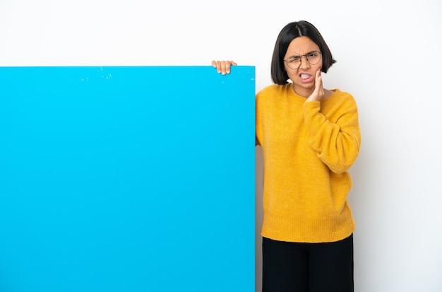 Jeune femme métisse avec une grande pancarte bleue isolée sur fond blanc avec mal de dents