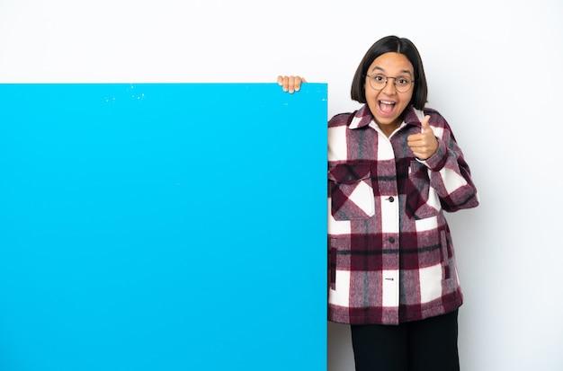 Jeune femme métisse avec une grande pancarte bleue isolée sur fond blanc montrant un signe ok et un geste du pouce vers le haut