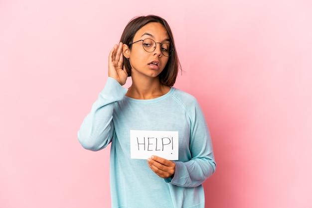Jeune femme métisse hispanique tenant une affiche d'aide essayant d'écouter un commérage.