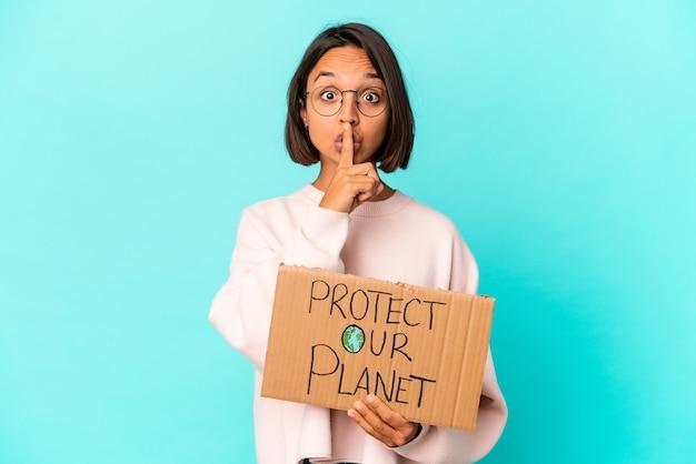 Jeune femme métisse hispanique tenant un carton de protection de notre planète en gardant un secret ou en demandant le silence.