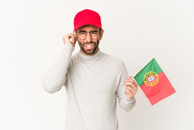 Jeune femme métisse hispanique tenant un drapeau du portugal couvrant les oreilles avec les mains