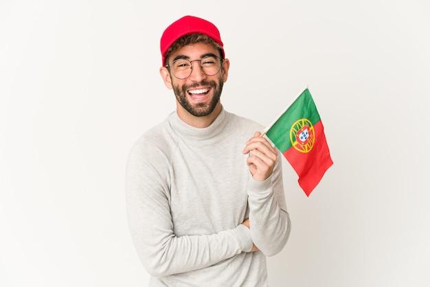Jeune femme métisse hispanique tenant un drapeau du portugal en riant et en s'amusant
