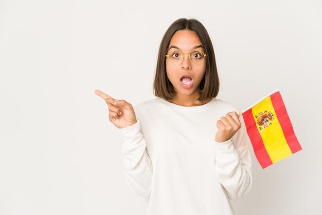 Jeune femme métisse hispanique tenant un drapeau espagnol pointant vers le côté