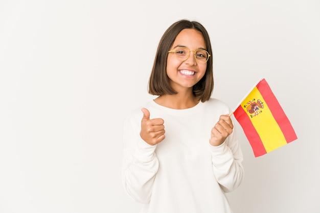 Jeune femme métisse hispanique tenant un drapeau espagnol souriant et levant le pouce vers le haut