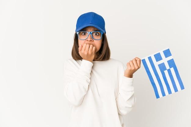 Jeune femme métisse hispanique tenant un drapeau de la grèce se mordre les ongles