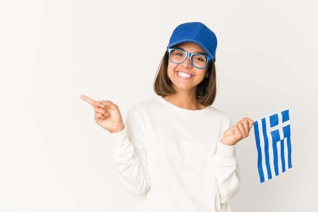 Jeune femme métisse hispanique tenant un drapeau de la grèce souriant et pointant de côté, montrant quelque chose à l'espace vide