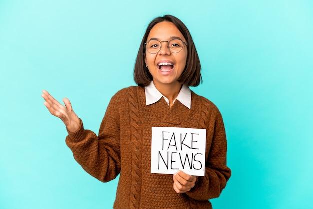 Jeune femme métisse hispanique tenant une pancarte de fausses nouvelles recevant une agréable surprise, excitée et levant les mains.