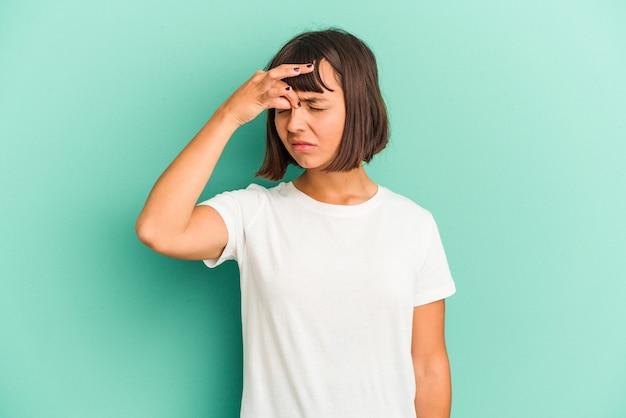 Jeune femme métisse isolée sur bleu ayant mal à la tête, touchant le devant du visage.