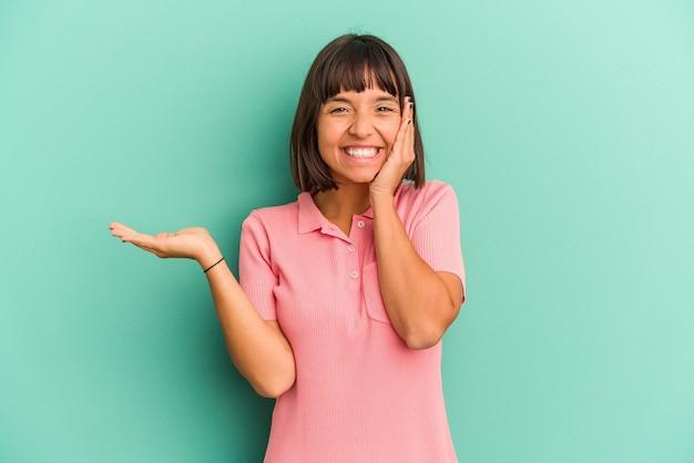 Jeune femme métisse isolée sur bleu détient un espace de copie sur une paume, gardez la main sur la joue. émerveillé et ravi.