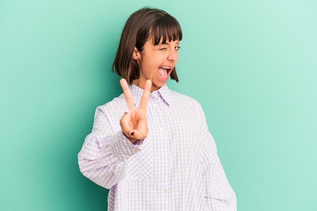 Jeune femme métisse isolée sur bleu montrant le numéro deux avec les doigts.