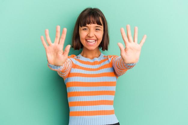 Jeune femme métisse isolée sur bleu montrant le numéro dix avec les mains.