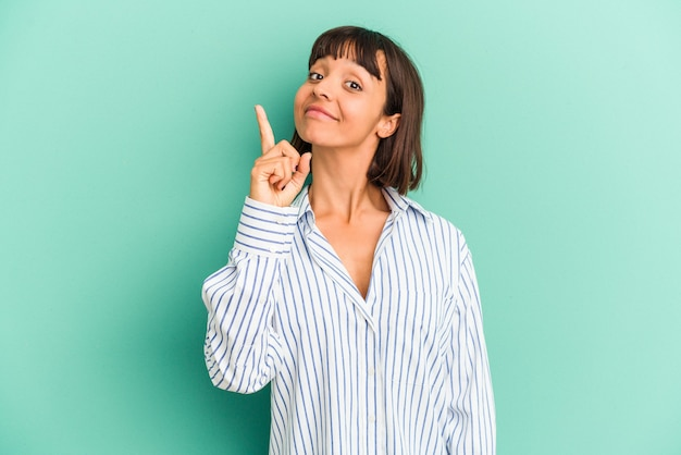 Jeune femme métisse isolée sur bleu montrant le numéro un avec le doigt.