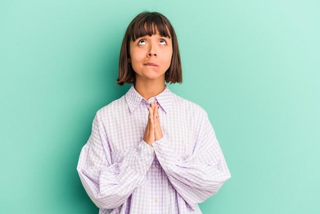 Jeune femme métisse isolée sur bleu se tenant la main dans la prière près de la bouche, se sent confiante.