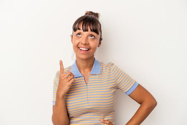 Jeune femme métisse isolée sur fond blanc indique avec les deux doigts antérieurs montrant un espace vide.
