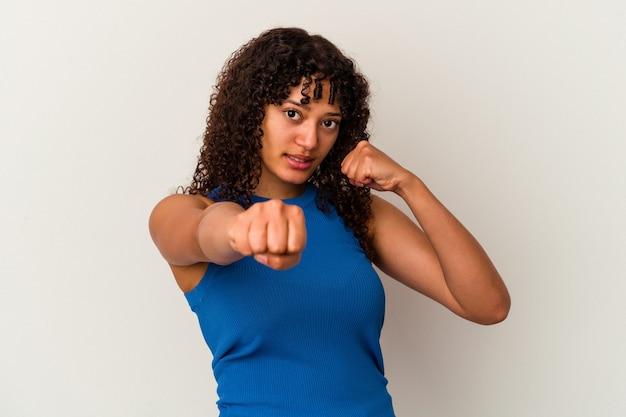 Jeune femme métisse isolée sur fond blanc jetant un coup de poing, colère, combat à cause d'une dispute, boxe.