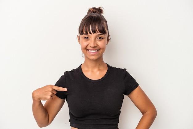 Jeune femme métisse isolée sur fond blanc personne pointant à la main vers un espace de copie de chemise, fière et confiante