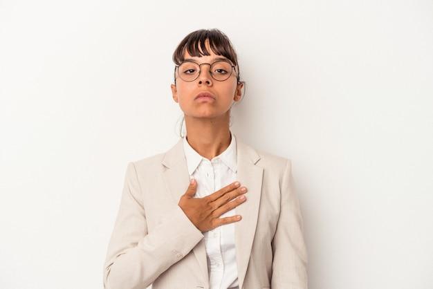 Jeune femme métisse isolée sur fond blanc prêtant serment, mettant la main sur la poitrine.