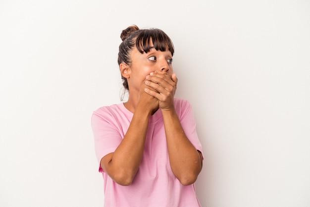 Jeune femme métisse isolée sur fond blanc réfléchie à la recherche d'un espace de copie couvrant la bouche avec la main.